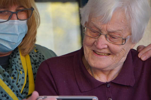 Nurse and grandmother looking at phone